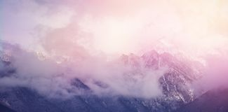 Clouds covering snowcapped mountains against sky. Scenic view of clouds covering snowcapped mountains against sky Stock Photography