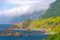 Clouds and Crags along an Ocean Coast Stock Image