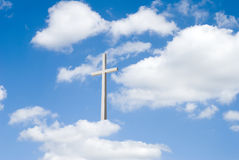 Clouds and Cross. A beautiful partly cloudy blue sky  with religious cross resting on clouds for background Royalty Free Stock Photos