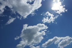 White Cumulus clouds on a blue sky background. Clouds Cumulus white on a blue sky background the sun shines from behind the clouds royalty free stock photography