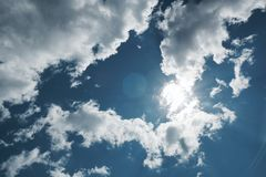 White Cumulus clouds on a blue sky background. Clouds Cumulus white on a blue sky background the sun shines from behind the clouds royalty free stock images