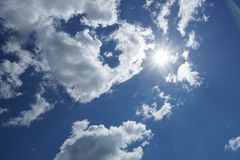 White Cumulus clouds on a blue sky background. Clouds Cumulus white on a blue sky background the sun shines from behind the clouds stock photos