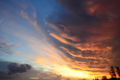 Clouds of different shapes and colors before sunset. Dramatic sky colors at sunset - blue, orange, golden. Royalty Free Stock Photography