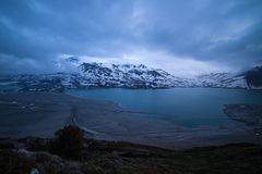 Clouds at dusk blue hour, lake and snowcapped mountain, cold winter, fjord nord landscape Stock Image
