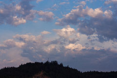 Clouds. In an evening blue sky over a darkening hill Royalty Free Stock Images
