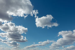 Clouds flying against blue sky at sunny day. Royalty Free Stock Image