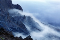Clouds and fog pass over rugged volcanic landscape in Volcanoes National park. Clouds and fog pass over rugged volcanic landscape Royalty Free Stock Photos