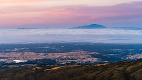 Clouds and fog at twilight over Silicon Valley and the San Francisco bay area; Stanford University visible under a layer of clouds stock images