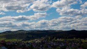 Clouds form in blue sky over small village. Time lapse stock footage