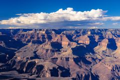 Clouds form over the famous Grand Canyon. The blue sky is populated with white clouds in the centre of this picture showing off the Grand Canyon in Arizona`s royalty free stock photography