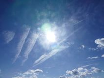 Clouds in formation. Bright blue sky with white fluffy clouds and bright sunlight Royalty Free Stock Photography