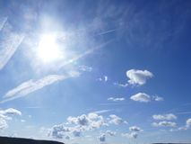 Clouds in formation. Bright blue sky with white fluffy clouds and bright sunlight Stock Image