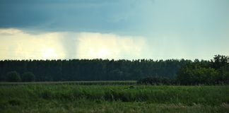 Clouds forming a storm over forest in distance royalty free stock photography