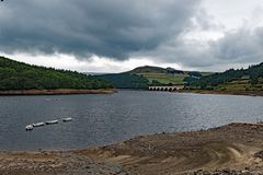 Clouds gather over the dry slopes and banks of Lady Bower reservoir in late summer. Taken to capture the scale of the water`s retreat at the Lady Bower royalty free stock image