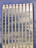 Clouds on Glass Building. Blue gray storm clouds are reflected off the glass of a tall modern building Royalty Free Stock Image