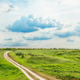 Clouds and green meadow with road Royalty Free Stock Photo