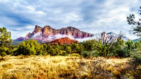 Clouds hanging around Lee Mountain and other red rock mountains surrounding the town of Sedona, Arizona stock photo