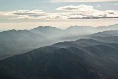 Clouds and Haze over Mountain Range. The  Jackknife Mountains in NWT, Canada viewed from an airplane with haze from local forest fires Stock Photos