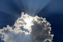 Clouds, High Resolution. A high resolution image of a cloud with sun rays peaking behind it, also a partial eclipse is behind the cloud August 21st, 2017 Royalty Free Stock Image