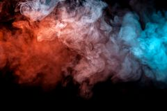 Clouds of isolated colored smoke: blue, red, orange, pink; scrolling on a black background in the dark stock photo