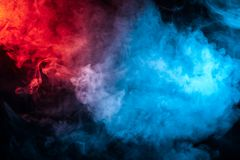 Clouds of isolated colored smoke: blue, red, orange, pink; scrolling on a black background. In the dark close up stock image