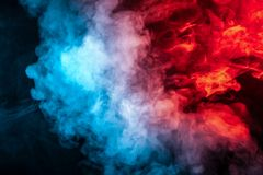 Clouds of isolated colored smoke: blue, red, orange, pink; scrolling on a black background in the dark. Close up stock image