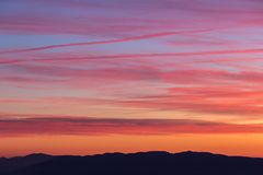 Clouds and jet vapor trails creating beautiful, colorful texture in the sky at sunset with mountain profiles on the low. Clouds and jet vapor trails creating Royalty Free Stock Photos