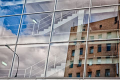 Clouds on a ladder. Reflection of the old house in glasses of the new building Royalty Free Stock Photo