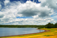 Clouds and lake. Beautiful cloudscape with some rain clouds, lake, and grass landscape royalty free stock images