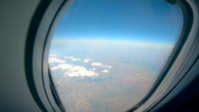 Clouds and land are shown from an aircraft. HD stock video footage