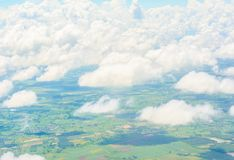 Clouds and land view from the window of an airplane Royalty Free Stock Photography