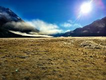 Clouds Lifting over a Field on Sunny Day. Clouds lifting on a Sunny Day over a field at the bottom of a mountain range in Fiordland National Park in New Zealand royalty free stock photos