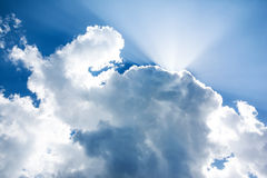 Clouds and lightbeams. Light-beams that shine out of clouds on a blue summer sky Royalty Free Stock Photography