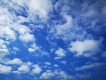 SOme clouds and blue sky. The clouds are like cotton in the sky. The sky is blue and clear in fall stock images