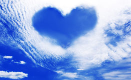 Clouds making a heart shape againt blue sky Stock Photo