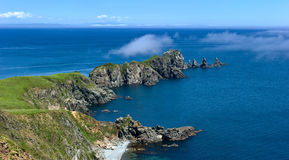 Clouds of mist creeps on a rocky promontory. Royalty Free Stock Images