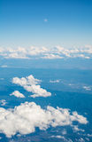 Clouds and moon in blue sky, aerial landscape view from airplane window. Royalty Free Stock Photos