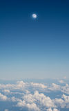 Clouds and moon in blue sky, aerial landscape view from airplane window. Royalty Free Stock Photo