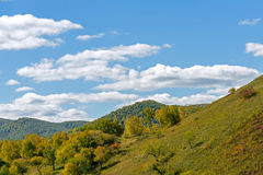Clouds and mountain forest in the autumn. This photo was taken in Hama (Frog) Dam scenic spot, WulanBu all grassland, Bashang Grassland, Hebei province, china royalty free stock images