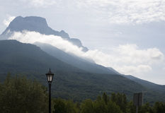 Clouds on the mountain, Pyrenees. Cloudscape in the Aragonese Pyrenees, Spain. In the foreground a lamppost and a signal Royalty Free Stock Image