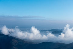 Clouds in mountain valleys under blue sky Royalty Free Stock Photography