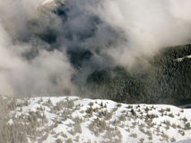 Clouds in the mountains. View from above on a  European spruce forest partially hidden by deep clouds.Between the clouds appears a mountain ridge and in the Royalty Free Stock Photography
