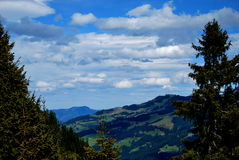 Clouds in the mountains. Clouds on the blue sky with needle trees in the austrian mountains Royalty Free Stock Photos