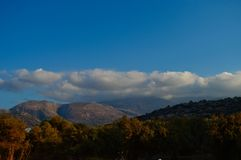 Clouds and mountains in Crete, Greece. Scenic landscape of the mountains of Crete and clouds with blue sky in the early autumn Stock Photography