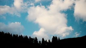 Clouds move above fir tree silhouettes in mountains. On background of light blue sky stock video footage