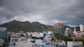 Clouds move from hills above white city time lapse. Time lapse grey clouds move from large mountains above beautiful modern white tropical resort city stock footage