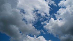 Clouds Move Smoothly in the Blue Sky. Timelapse. Sunny blue sky, white, and gray clouds. Beautiful clouds flying in the air. Time lapse. Atmospheric weather stock footage