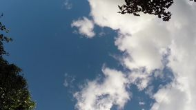Clouds moving across bright blue sky stock footage