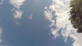Clouds moving across bright blue sky stock video footage