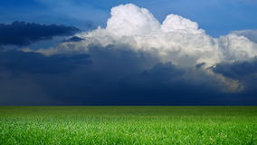 Clouds moving over a green field Stock Photography